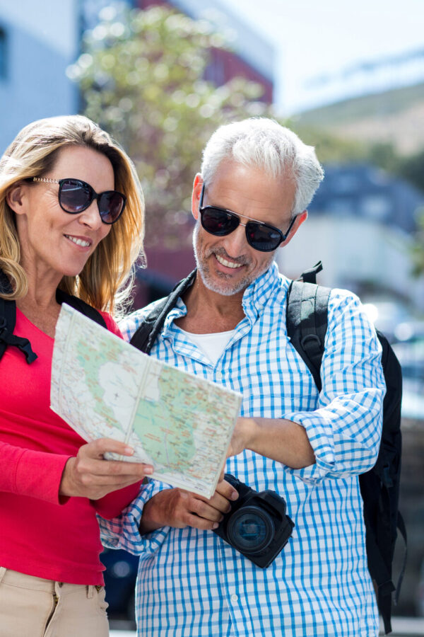 Happy mature couple reading map in city